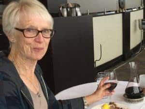Marilyn Wood sits at a table with a glass of wine.